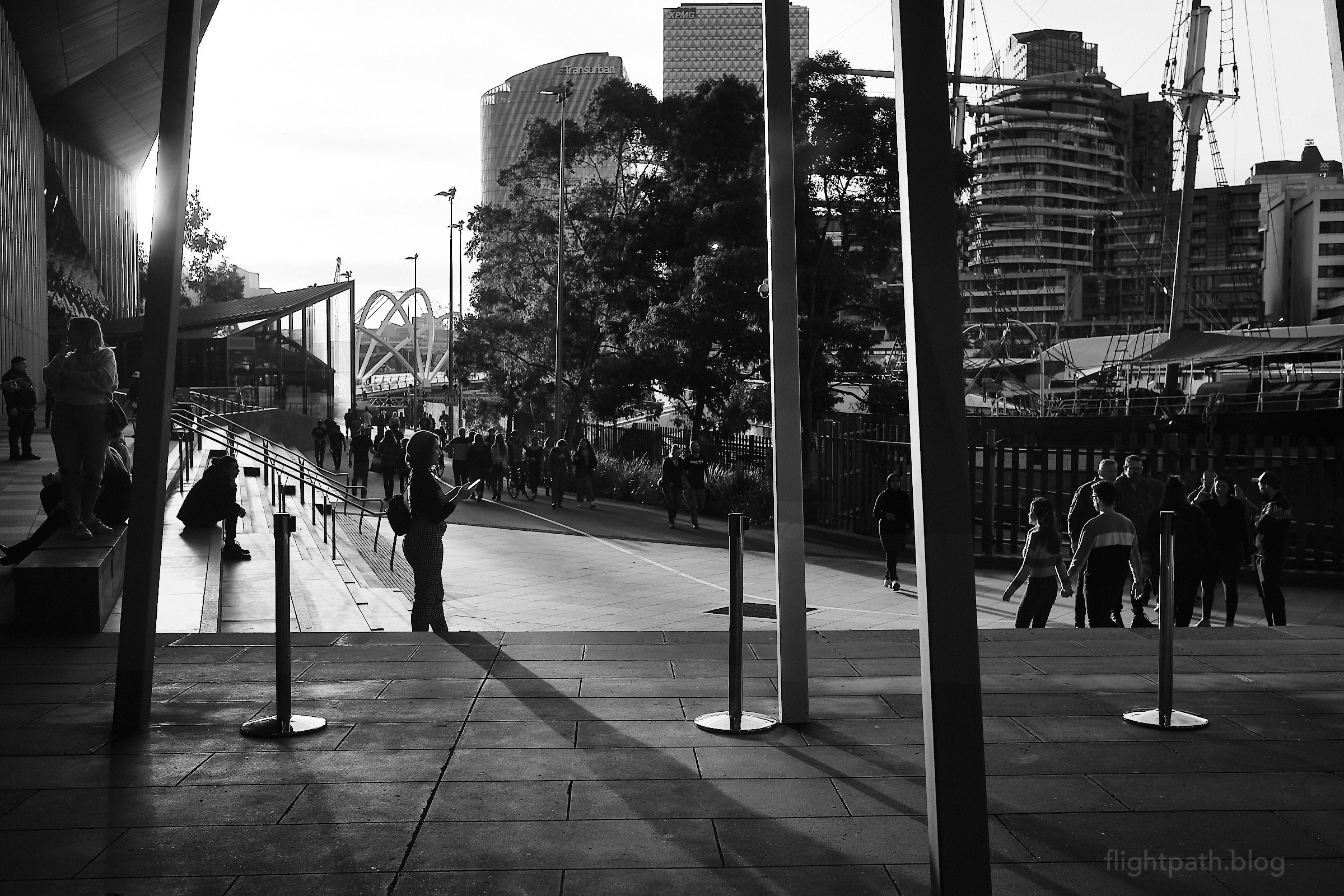 """A number of people are milling about outside the Melbourne Convention Centre. A woman in near-silhouette is using her phone. The word """"urban"""" can be seen on a building."""
