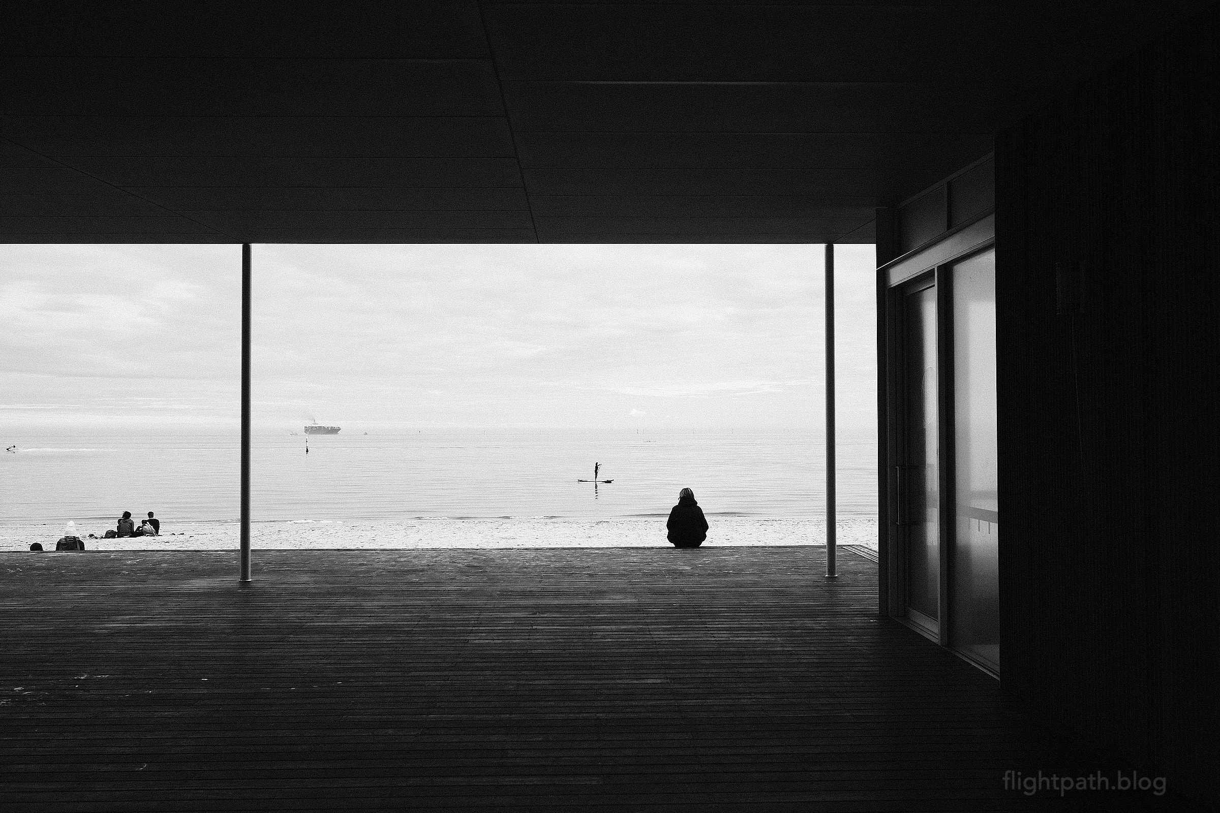 Framed by a wooden deck and pavilion, a person sits on the beach dressed for winter. They are watching a person in the calm water on a stand-up paddle board.