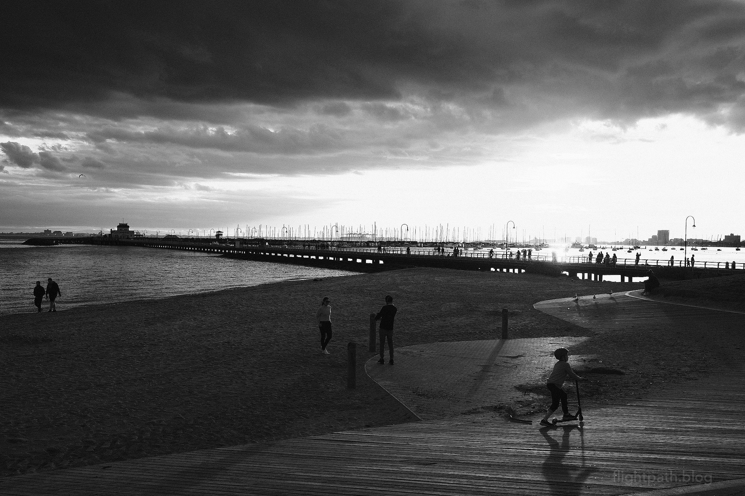 A view of St Kilda Pier with the sun low on the horizon. Silhouettes of various people are shown on the beach and pier.