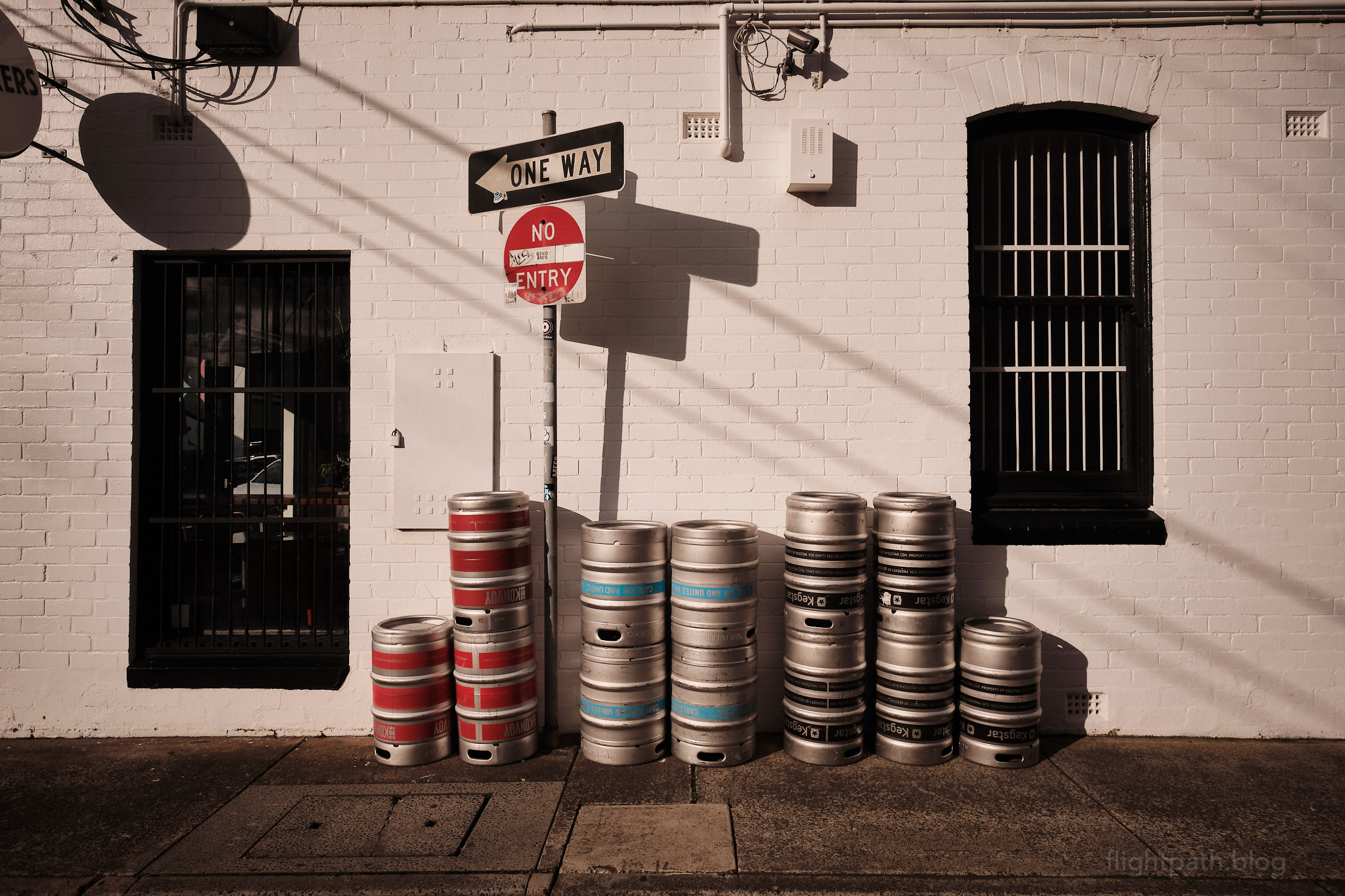 """Stacks of empty beer kegs sit on the footpath beside a pub. A street sign reads """"ONE WAY"""" and """"NO ENTRY"""". There is a sticker on the sign with the faint text """"DTRAIN""""."""