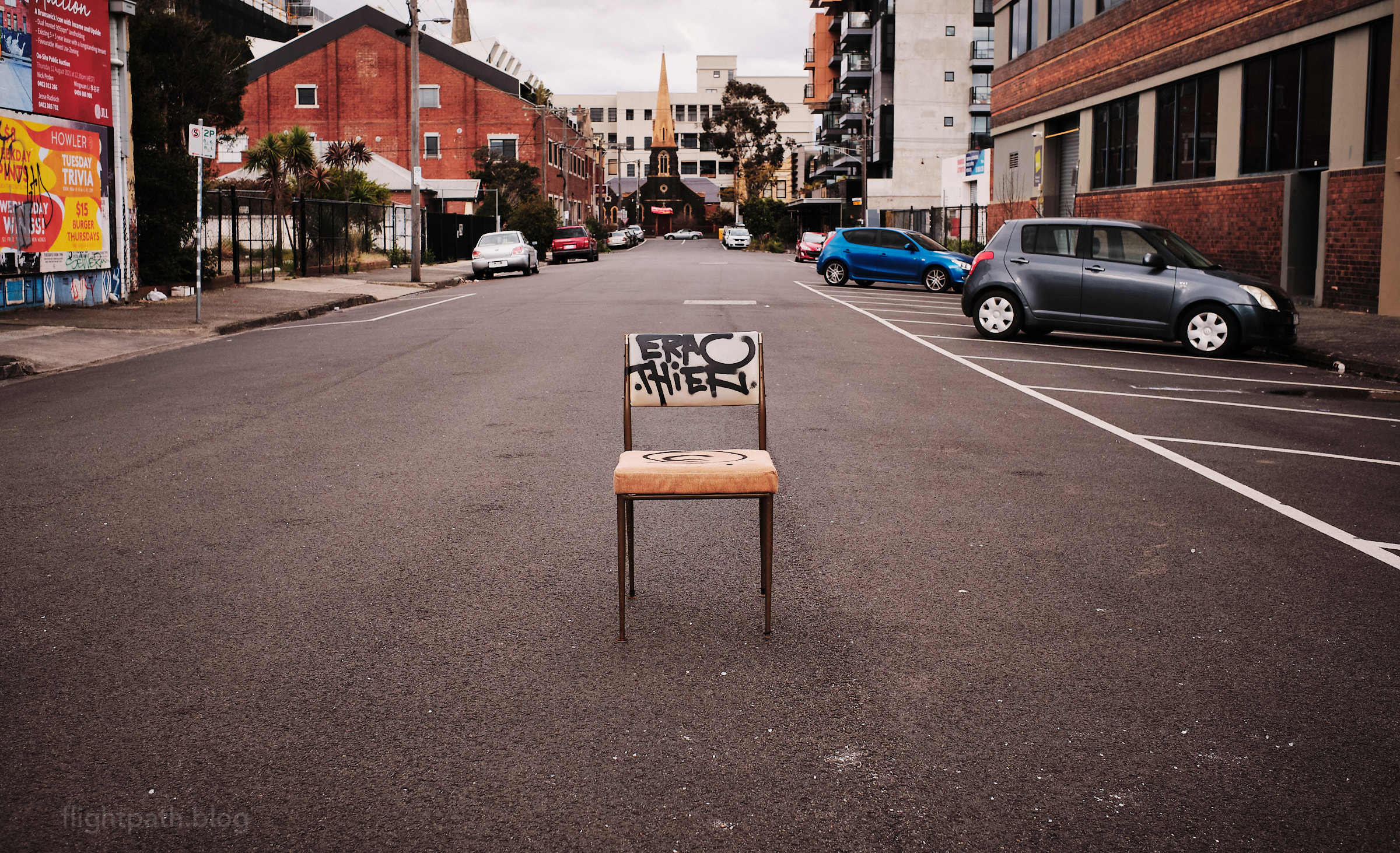 """A faded chair sits inexplicably in the middle of a side road. There is crude graffiti on the chair. A real estate advertisement in the background includes the words """"Brunswick Icon""""."""